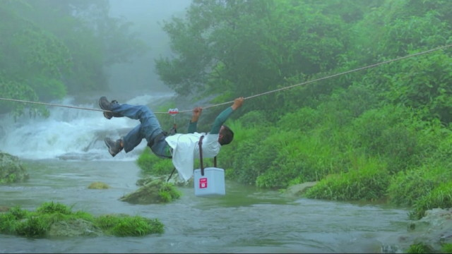 vakcinaszállítás Indiában, folyó felett mászva